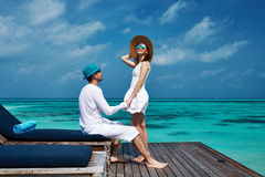 Couple on a beach jetty at Maldives. Couple on a tropical beach jetty at Maldives Stock Photos