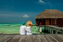 Couple on a beach jetty at Maldives Stock Image