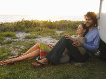 Couple On Beach Leaning On Campervan. Full length of young couple on beach leaning on campervan royalty free stock image