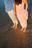 Couple on the beach. Legs on beach. Foot spa. Two lovers, man and woman barefoot near the water. Summer in love Royalty Free Stock Photography