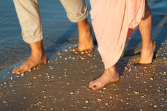 Couple on the beach. Legs on beach. Foot spa. Two lovers, man and woman barefoot near the water. Summer in love Stock Photos