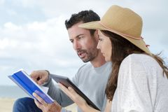 Couple on beach looking at book and tablet royalty free stock photo
