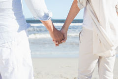 Couple on the beach looking out to sea holding hands Royalty Free Stock Image