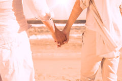 Couple on the beach looking out to sea holding hands Royalty Free Stock Images