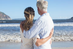Couple on the beach looking out to sea Stock Image