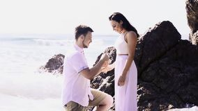 Couple at the beach with man proposing, stock footage