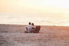Couple at Beach Near Cooler Royalty Free Stock Photography