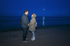 Couple on beach at night. Couple wearing winter coats on a beach at night royalty free stock image