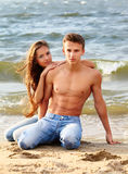 Couple at the beach. Outdoor portrait of beautiful romantic couple of topless girl and muscular guy in jeans on beach Stock Photos