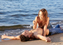 Couple at the beach. Outdoor portrait of beautiful romantic couple of topless girl and muscular guy in jeans on beach. girl drops sand on guys chest Royalty Free Stock Images