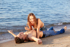 Couple at the beach. Outdoor portrait of beautiful romantic couple of topless girl and muscular guy in jeans on beach. girl drops sand on guys chest Stock Photo