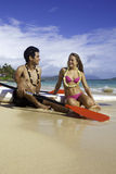 Couple on the beach with paddleboards Stock Photos