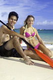 Couple on the beach with paddleboards Royalty Free Stock Images