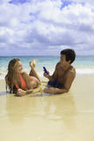 Couple on the beach photographing Royalty Free Stock Photography