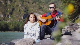 Couple on the beach playing guitar sings song on a summer day next to mountain river. 1920x1080 stock footage