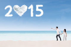 Couple on beach pointing at number 2015 Stock Photo
