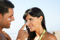 Couple on the beach  putting on cream Royalty Free Stock Image