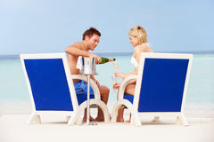 Couple On Beach Relaxing In Chairs And Drinking Champagne Stock Images