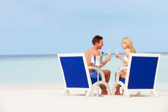 Couple On Beach Relaxing In Chairs And Drinking Champagne. Smiling royalty free stock images