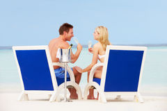 Couple On Beach Relaxing In Chairs And Drinking Champagne Stock Image