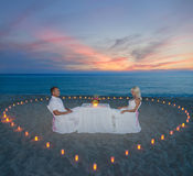Couple at beach romantic dinner with candles heart Stock Photography