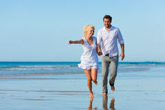 Couple on the beach running into glorious future. Couple on the beach in white clothing running down, they might be on vacation or even honeymoon Royalty Free Stock Photography