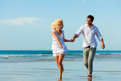 Couple on the beach running into glorious future. Couple on the beach in white clothing running down, they might be on vacation or even honeymoon Stock Photo