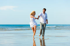 Couple on the beach running into glorious future. Couple on the beach in white clothing running down, they might be on vacation or even honeymoon Royalty Free Stock Photos