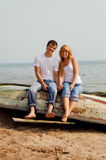 Couple on a beach sitting on old boat Stock Images