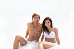 Couple on beach, sitting in water wave foam sea Stock Photography