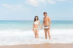 Couple on beach standing in water wave foam Stock Photo