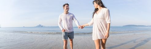 Couple On Beach Summer Vacation, Beautiful Young Happy People In Love Walking, Man Woman Smile Holding Hands. Sea Ocean Holiday Travel stock image