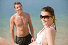 Couple on beach - sunbathing in swimsuit by sea Stock Photography