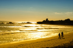 Couple on the beach at Sunset. Sunset on the Pacific Ocean while a couple walk on the Malibu beach in California Royalty Free Stock Photo