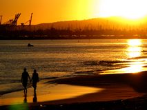 Couple on beach at sunset. A silhouetted view of a couple walking hand-in-hand on a beach at sunset with silhouettes from an industrial seaport in the background Royalty Free Stock Images