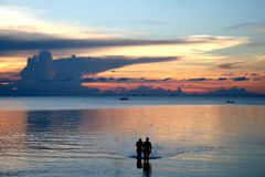 Couple on the beach - Sunset. A playful romantic couple taking in the sunset at a resort on Ko Pha-Ngan island in Thailand Royalty Free Stock Image