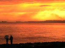 Silhouetted couple on beach stock image
