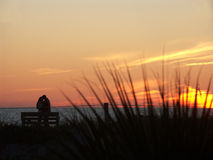 Couple on the beach at sunset. A loving couple standing along the ocean, on a sandy beach, watching the colorful sunset Royalty Free Stock Images