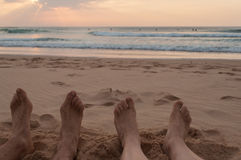 Couple in the beach at sunset. Foot view Royalty Free Stock Images