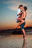 Couple on the beach at sunset Stock Photos