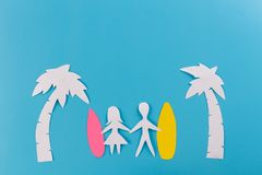 Couple on the beach with surfboards. Paper cut stock image