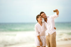 Couple on the beach taking photo of themselves Royalty Free Stock Photo
