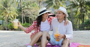 Couple On Beach Talking Drink Juice Sit Embracing Under Palm Trees, Happy Man And Woman Tourist Communication. Slow Motion 60 stock video