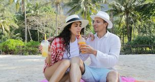 Couple On Beach Talking Drink Juice Talking Sit Under Palm Trees, Happy Man And Woman Kissing. Slow Motion 60 stock video