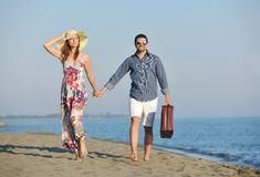 Couple on beach with travel bag Stock Photo