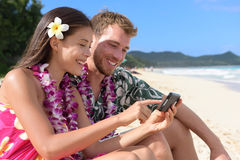 Couple on beach using smart phone on Hawaii Royalty Free Stock Photos