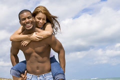 Couple on beach vacation. African American holding Hispanic girl. Man without shirt, both wearing jeans.  Blue sky in the background Royalty Free Stock Images