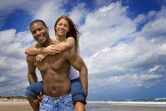 Couple on beach vacation. African American holding Hispanic girl. Man without shirt, both wearing jeans.  Blue sky in the background Royalty Free Stock Photography
