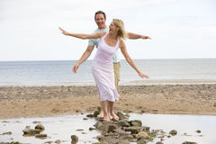 Couple at the beach walking on stones and smiling royalty free stock photos