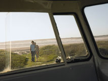 Couple On Beach Walking Towards Campervan Stock Image